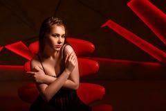 Belle femme dans la chaise rouge posant dans le studio photographie stock