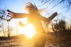 Belle femme dans la danse rouge d'écharpe dans le coucher du soleil Automne Image libre de droits