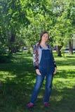 belle femme dans la grossesse tôt dans la combinaison de denim, se tenant sur l'herbe verte en parc photos libres de droits