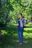 belle femme dans la grossesse tôt dans la salopette de denim, se tenant sur l'herbe verte en parc photos stock