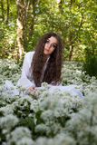 Belle femme dans la longue robe blanche se reposant dans une forêt Photos stock