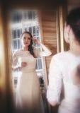 Belle femme dans la longue robe de mariage regardant dans le miroir photographie stock