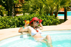 Belle femme dans la piscine avec le cocktail Image libre de droits