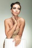 Belle femme dans la robe élégante tenant sa main sur le cou Photographie stock