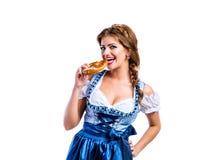 Belle femme dans la robe bavaroise traditionnelle tenant un bretzel Images stock