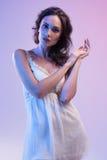 Belle femme dans la robe blanche et la lumière bleue sur le fond bleu Photo libre de droits