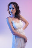Belle femme dans la robe blanche et la lumière bleue sur le fond bleu Images libres de droits