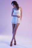 Belle femme dans la robe blanche et la lumière bleue sur le fond bleu Images stock