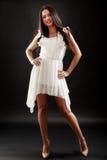 Belle femme dans la robe blanche sur le noir Image stock