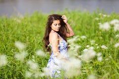 Belle femme dans la robe bleue parmi des wildflowers photographie stock libre de droits
