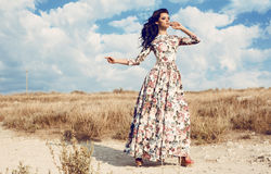 Belle femme dans la robe florale luxueuse posant dans le domaine d'été Image libre de droits