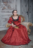 Belle femme dans la robe médiévale sur le fauteuil Photo stock