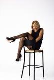 Belle femme dans la robe noire posant se reposer sur une chaise Photographie stock libre de droits