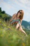 Belle femme dans la robe se reposant sur l'herbe et ayant l'amusement Images stock