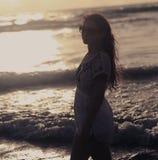 Belle femme dans la robe se tenant en mer et regardant sur les soleils Photo stock