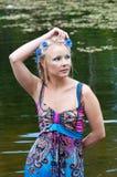 Belle femme dans la robe se tenant près de l'étang Photographie stock