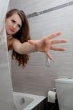 Belle femme dans la salle de bains streching pour le somethin Photos stock