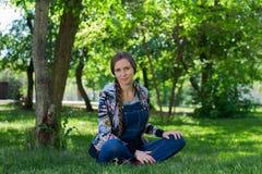 belle femme dans la salopette de denim se reposant sur l'herbe verte en parc photo libre de droits