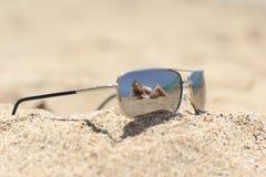 Belle femme dans le bikini s'exposant au soleil sur la plage Photographie stock libre de droits