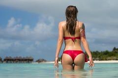 Belle femme dans le bikini sexy au-dessus du fond de plage photographie stock libre de droits