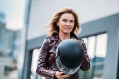 belle femme dans le casque de moto de participation de veste en cuir sur la rue photo libre de droits