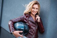 belle femme dans le casque de moto de participation de veste en cuir sur la rue et le regard image stock