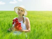 Belle femme dans le chapeau au soleil sur un champ de seigle Images stock