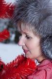 Belle femme dans le chapeau de fourrure d'hiver sur l'arbre de Noël rouge de fond Photo stock