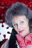 Belle femme dans le chapeau de fourrure d'hiver sur l'arbre de Noël rouge de fond Photos stock