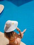 Belle femme dans le chapeau se reposant sur le bord de la piscine Photos stock