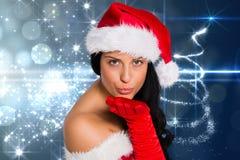 Belle femme dans le costume de Santa soufflant un baiser sur le fond digitalement produit de Noël Photo stock