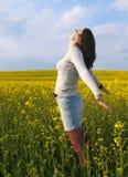 Belle femme dans le domaine avec les fleurs jaunes. Photographie stock libre de droits