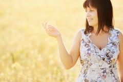 Belle femme dans le domaine de blé au coucher du soleil Photo libre de droits