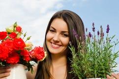 Belle femme dans le jardin avec des fleurs. Images stock