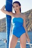 Belle femme dans le maillot de bain détendant sur le yacht en mer ouverte Images stock