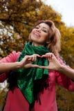 Belle femme dans le manteau rose montrant le coeur dans le parc Photos stock