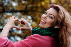 Belle femme dans le manteau rose montrant le coeur dans le parc Image libre de droits