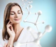 Belle femme dans le peignoir près de la grande chaîne blanche de molécule Image libre de droits