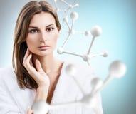 Belle femme dans le peignoir près de la grande chaîne blanche de molécule Image stock