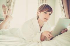 Belle femme dans le peignoir se trouvant sur un lit Photo libre de droits