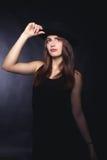 Belle femme dans le rétro style avec le chapeau noir de Mafia - image courante Photos stock