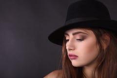 Belle femme dans le rétro style avec le chapeau noir de Mafia - image courante Images libres de droits