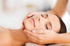 Belle femme dans le salon de station thermale ayant le massage facial Photographie stock