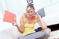 Belle femme dans le salon prenant des notes. photographie stock libre de droits