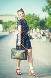 Belle femme dans le style d'années '50 avec des accolades tenant le rétro camer Photo libre de droits