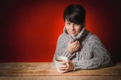 Belle femme dans le thé potable de chandail Photographie stock