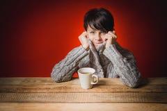 Belle femme dans le thé potable de chandail Photos libres de droits