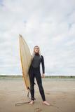 Belle femme dans le vêtement isothermique tenant la planche de surf à la plage Photographie stock libre de droits