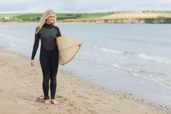 Belle femme dans le vêtement isothermique tenant la planche de surf à la plage Images stock