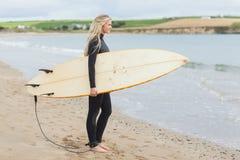 Belle femme dans le vêtement isothermique tenant la planche de surf à la plage Images libres de droits
